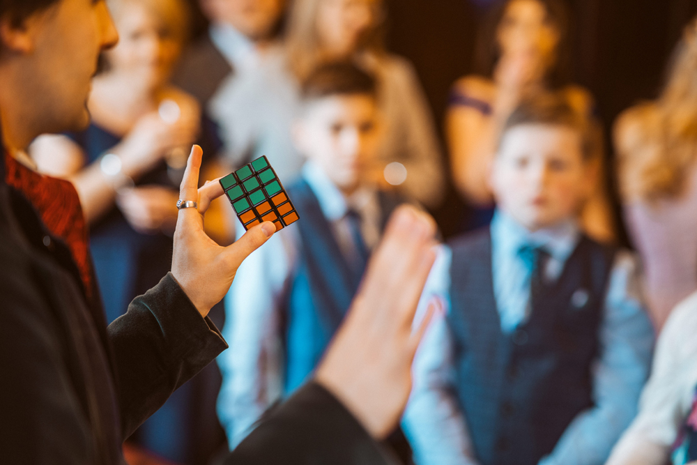 A close up of a magician holding a Rubick's cube, with wedding guests in the background