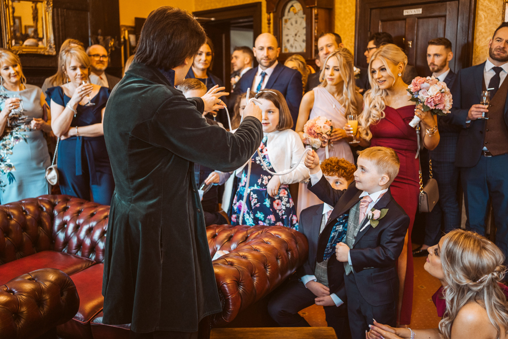 Guests at a wedding being entertained by a magician