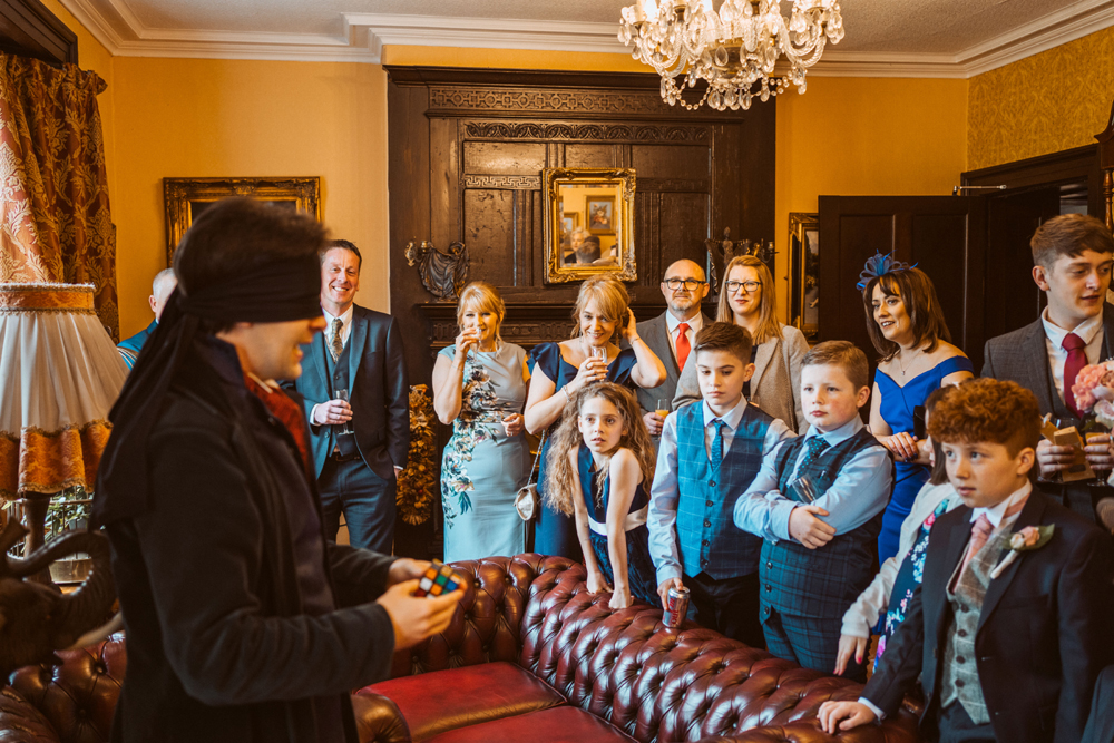 Guests at a wedding watching a magician perform