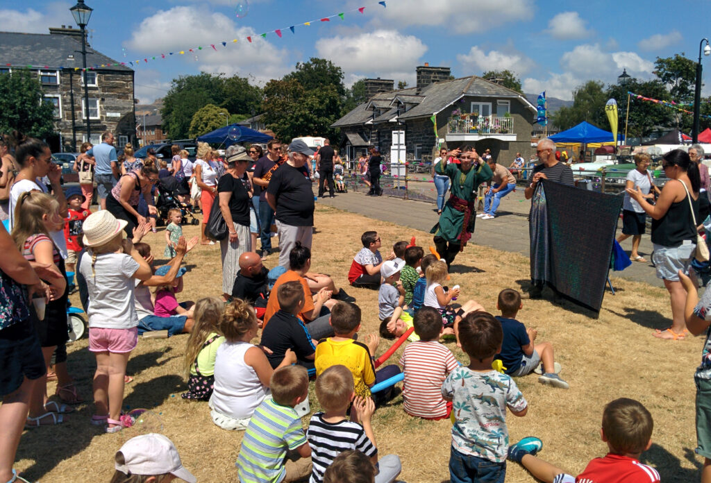Jay Gatling as the Wizard of Conwy, performing to a crowd of people on a beautiful sunny day.
