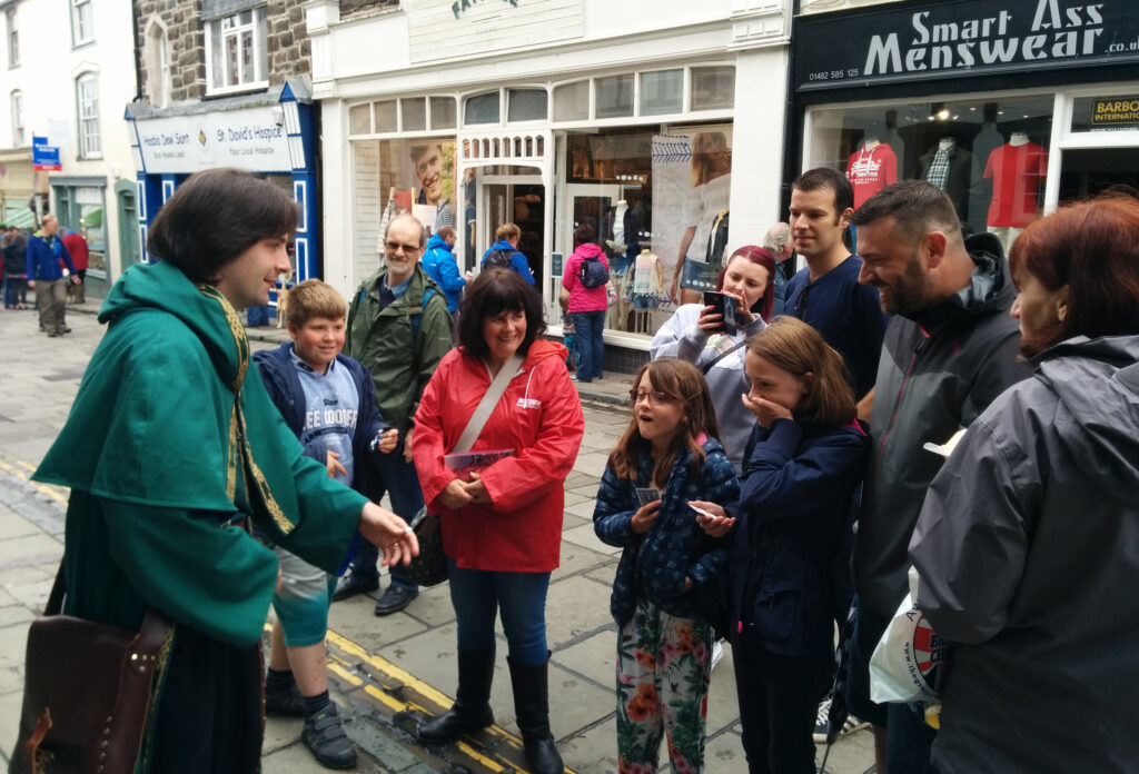 Jay Gatling as The Wizard of Conwy performs to an appreciative audience on a rainy street.