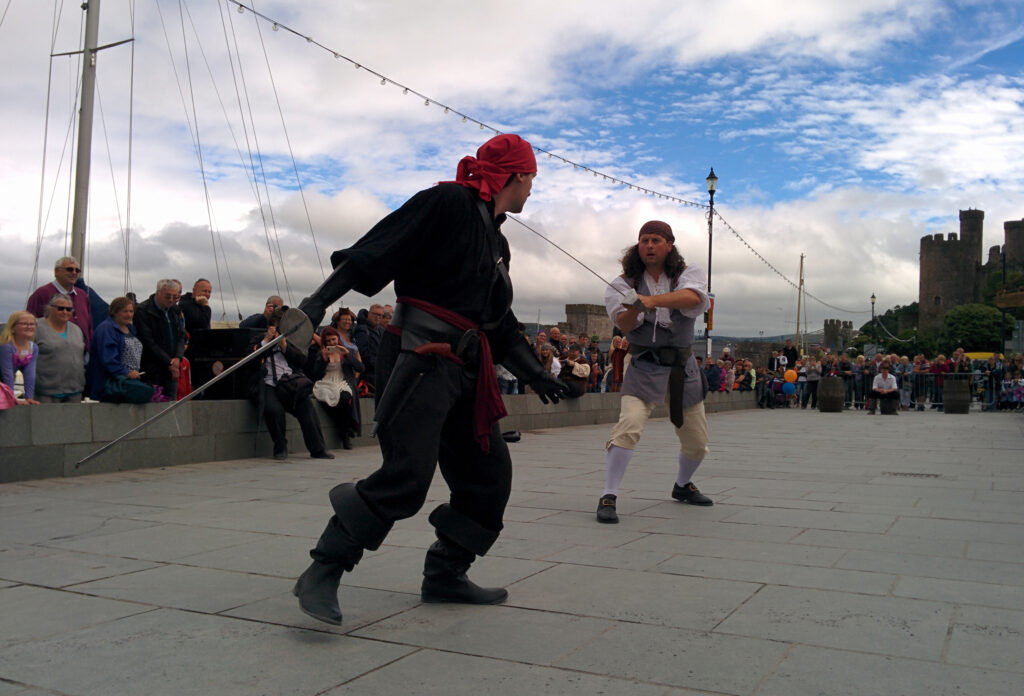 Jay Gatling and Erwyd in the middle of a sword fight, surrounded by an audience of hundreds.