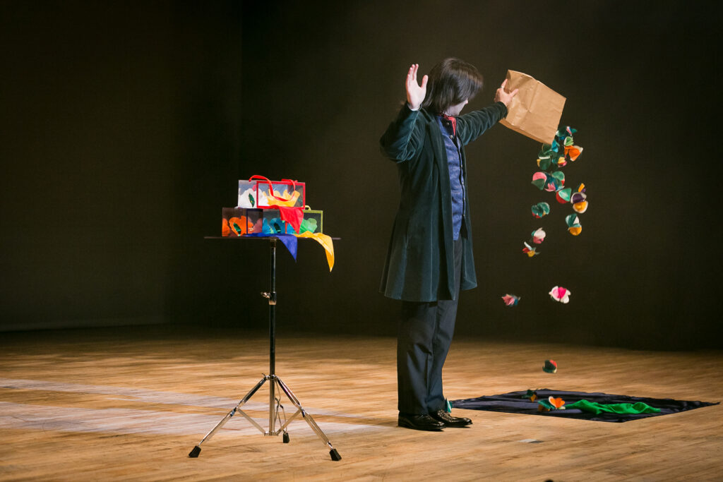 Jay Gatling performing magic on stage, producing flowers from an empty bag.