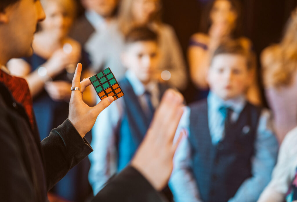 Close up of Jay Gatling doing magic with a Rubik's Cube, with wedding guests in the background.