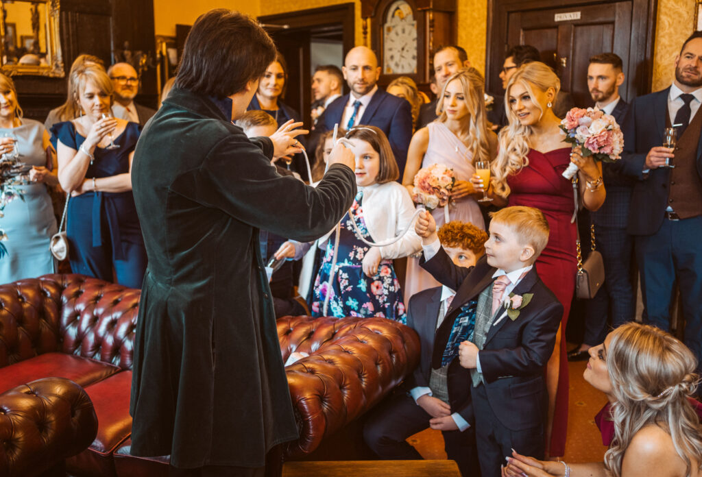 Jay Gatling performing a parlour show to a room of wedding guests.