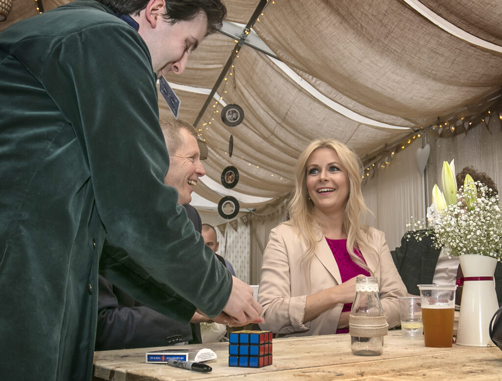 Magician Jay Gatling shows a smiling woman a card trick at a wedding in North Wales