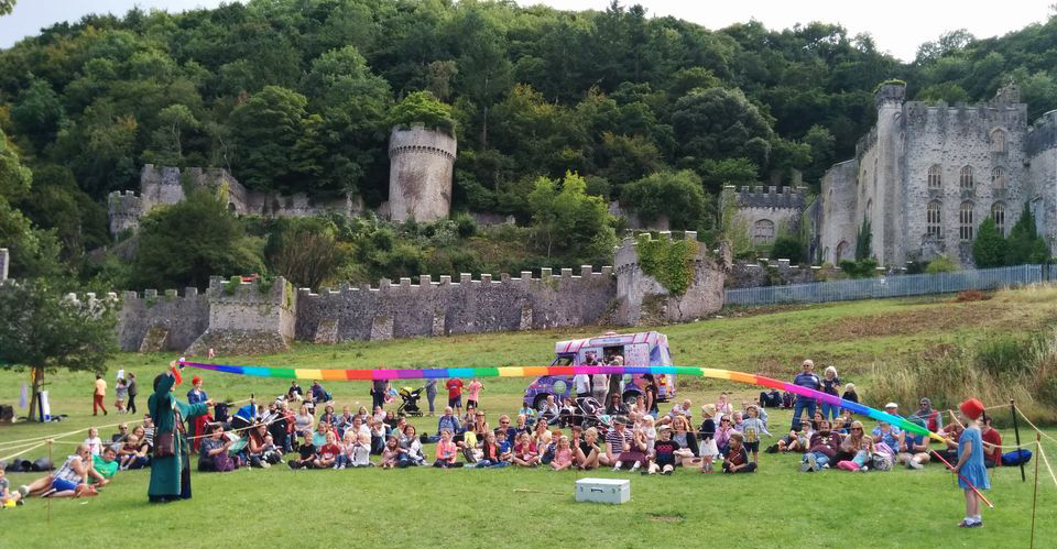 A crowd watching a magician perform at Gwrych Castle; a long rainbow streamer is held between the magician and a child, billowing in the wind